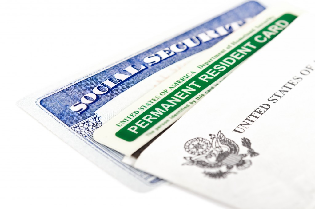 United States of America social security and green card on white background. Immigration concept. Closeup with shallow depth of field.
